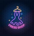 dress shop neon light sign on dark brick wall vector image