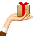 womans hand holding gold gift box with red ribbon vector image vector image
