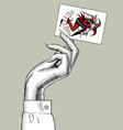 hand of woman holding joker playing card vector image