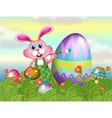 A bunny painting the egg in the garden vector image vector image