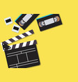 movie clapper and video cassette tapes on yellow vector image vector image