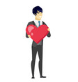 asian groom holding a big red heart vector image vector image