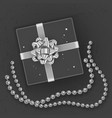 a realistic black gift box decorated with a silver vector image