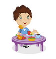 cute smiling cartoon boy eat chiken at table vector image