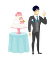 Groom standing near cake with glass of champagne