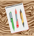 notebook green pen red pen and yellow pen vector image