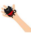 hand arm holding black cat with red bow ribbon vector image