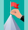businessman hand puts flag on peak mountain vector image