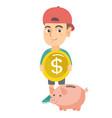 caucasian boy putting a coin into a piggy bank vector image