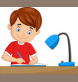 cartoon little boy studying on table vector image vector image