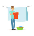 young smiling man hanging wet clothes out to dry vector image