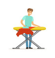 young smiling man ironing clothes on ironing board vector image
