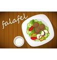 Plate of falafel on wooden table Top view vector image