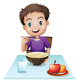 A boy eating his breakfast at the table vector image vector image