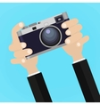Retro photo camera with hand holding it vector image