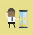 businessman is looking at hourglass with gold coin vector image vector image