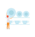 young man putting the plates on the shelf vector image