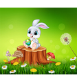 Cartoon Easter Bunny painting an egg on tree stump vector image vector image