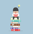 Businessman sitting on the stack of book and read vector image