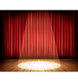 A theater stage with a red curtain and a spotlight vector image