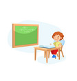 little schoolboy character sitting at desk vector image vector image