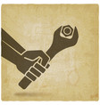 hand with spanner tightening nut on vintage vector image vector image