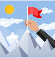 businessman hand puts flag on peak of mountain vector image vector image