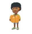 african boy standing with a big orange pumpkin vector image vector image