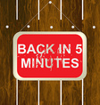 Back in 5 minutes sign hanging on a wooden fence vector image vector image