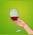 hand holding glass of red wine pop art retro pin vector image vector image