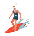 Bearded male surfer in red santa hat riding waves