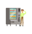 young man standing next to automatic vending vector image