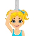 Happy little girl measuring her growth in height vector image