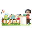 A boy with a frame in front of the hanging clothes vector image vector image