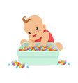 cute happy baby sitting and playing with box full vector image vector image