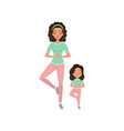 young curly-haired mother with daughter doing yoga