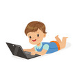 happy little boy lying on the floor using laptop vector image vector image