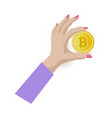 female hand holding bitcoin golden coin in fingers vector image