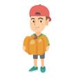 caucasian boy standing with a big orange pumpkin vector image