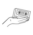 hand holding cassette black and white vector image