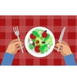 Salad and hands holding knife and fork vector image