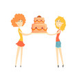 two smiling young women holding festive cake vector image vector image