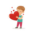 cute little boy holding red heart happy vector image
