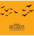 yellow happy halloween background with flying bats vector image vector image
