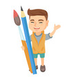 smiling boy holding big pencil and paintbrush vector image vector image