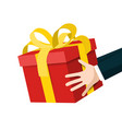 hands holding red gift box with gold bow vector image vector image