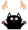 black cat face looking up to human hand paw print vector image