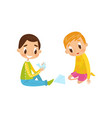 cute little boy and girl sitting on the floor vector image