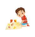 cute little boy sitting on his knees and painting vector image vector image
