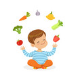 smiling little boy sitting on the floor juggling vector image vector image